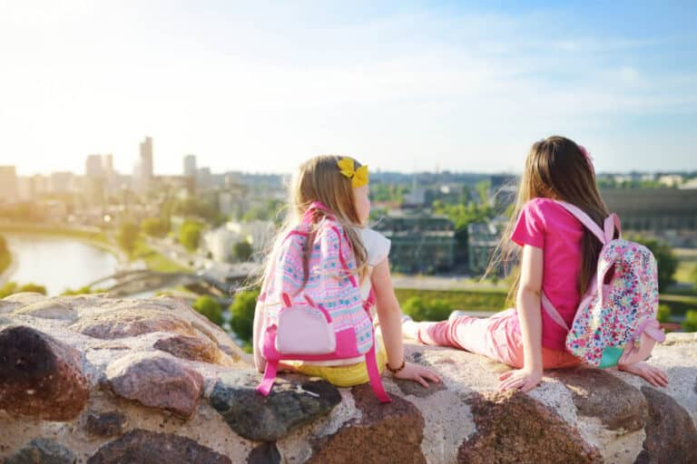 Cute little girls enjoying a view of Vilnius city from the Gediminas hill. Exploring tourist attractions with kids.
