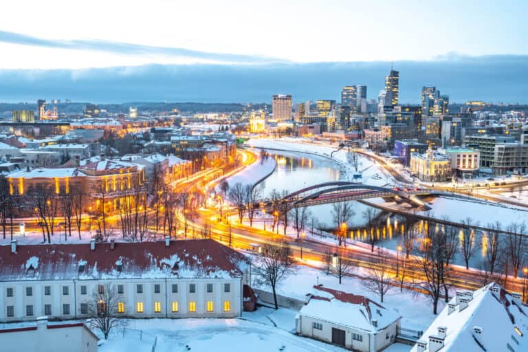Vilnius, capital of Lithuania, beautiful scenic aerial panorama of modern business financial district architecture buildings with river and bridge in winter, Global City of the Future