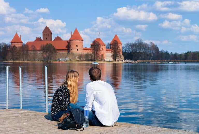 Young couple looking at Trakai island castle at Galve lake, near Vilnius, Lithuania
